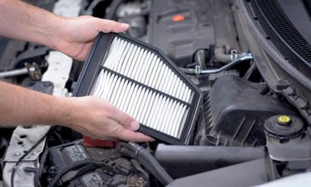 mechanic placing new air filter in car