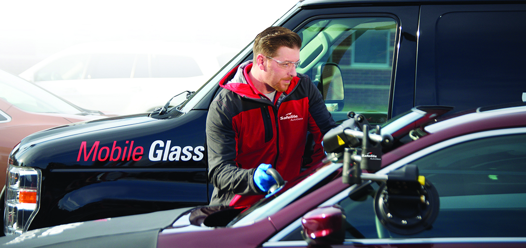 Auto glass technician expertly installing a new windshield on site